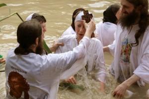 Chrisitian orthodox priests baptize a pi