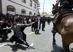 TOPSHOTS Anti-Zionist, Ultra-Orthodox Jewish men clash with Israeli police as they protest against the removal of ancient tombs in Jaffa, just south of Tel Aviv, on June 16, 2010 where construction is due to take place at the site where religious men say Jewish graves are located. AFP PHOTO/JACK GUEZ (Photo credit should read JACK GUEZ/AFP/Getty Images)(Photo Credit should Read /AFP/Getty Images)